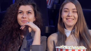 Two caucasian girls sharing impressions at the movie theater. Attractive curly woman telling something to her friend at the cinema. Pretty female teen agreeing with her friend