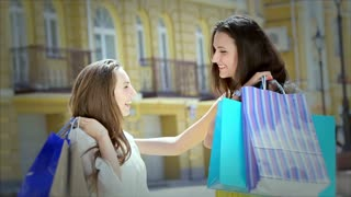 Two cute girls meet while shopping and a friendly hug