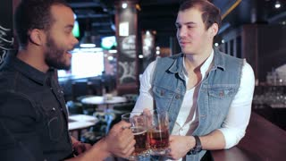 Two friends at the bar with beer glasses ring