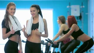Two girl posing in the gym and look into the camera showing a thumbs up
