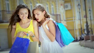 Two girls considering fashionable shopping in bags