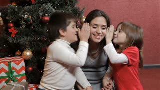 Two kids wisper into woman's ears near the christmas tree