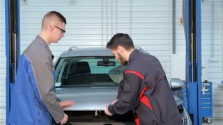 Two mechanics open the car hood at the car service