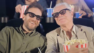 Two men watching 3D film at the movie theater