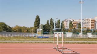 Two sprinters jump over the hurdles at the stadium