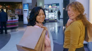 Two women turning back to the camera at the mall. Caucasian and asian ladies finishing their shopping. Two attractive female shoppers smiling for the camera with shopping bags on their shoulders