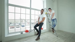 Two young builders standing at the ladder