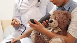 A close-up view of doctor measure the girl s blood pressure. The girl is sitting at doctor's appointment. In her hands she holds her soft bear and a stopwatch. Her doctor is sitting next to her