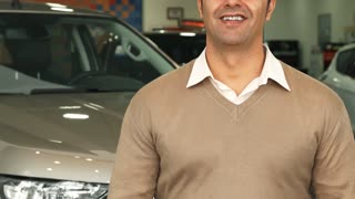 A man stands in the background of one of the cars in the car dealership. He raises his hand and shows the keys to the car. The video shows only the torso and the hands of a man