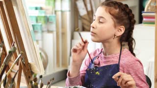 Adorable cheerful little girl examining her painting smiling to the camera showing thumbs up enjoying art class at her school childhood creativity children drawing imagination joy.