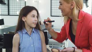 Adorable cheerful little girl smiling to the camera her mom applying makeup on her face kids actors pampering beauty fashion style skin cosmetics artist visage childhood occupation job.