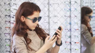 Adorable cheerful little girl wearing sunglasses taking selfies at the optometrist store buying consumerism social media children fun smart phone mobility eyewear optics sales retail