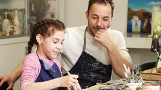 Adorable little girl drawing at art studio her loving happy father smiling cheerfully taking photos of his daughter with a smart phone family technology happiness love bonding artist painting.