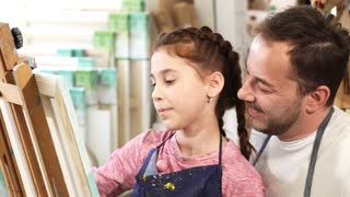 Adorable little girl enjoying painting with her dad at art class. Mature happy man taking selfies with his cute young daughter while she is painting on easel technology lifestyle family love social