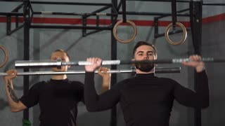 Athletic men working out at the gym together lifting barbells. Handsome bearded crossfit athlete exercising at crossfit box fit his male friend. Bodybuilding, weightlifting, motivation, sports concept