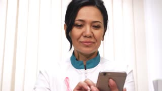 Attractive mature female Asian doctor smiling using her smart phone at the clinic wearing pink ribbon breast cancer awareness sign emotions online internet carrier mobility technology