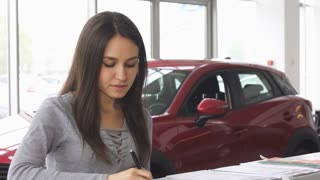 Attractive woman buying a new car at the dealership and signing papers for insurance. Young female customer filling documents for her new automobile. Consumerism, ownership concept.
