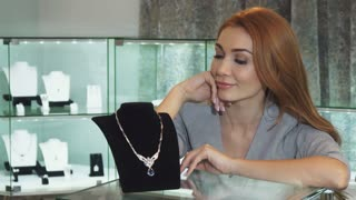 Attractive young happy woman smiling joyfully examining expensive diamond necklace at the jewelry store sales discount offer retail consumerism client shopping buying consumer