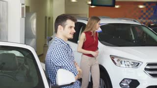 Attractive young man posing near his newly bought automobile showing car keys to the camera. Happy male driver at the dealership showroom. Consumerism, rental, driving concept.
