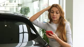 Attractive young red haired woman smiling happily talking on the phone while shopping for a new car at the dealership transport automotive industry buying consumerism communication