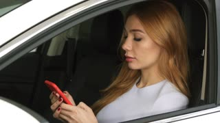 Attractive young sexy woman using smart phone sitting in her car smiling to the camera technology communication safety driving online automotive rental service connection mobility travelling