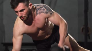Bearded muscular male crossfit athlete with hot fit and toned perfect body working out with dumbbells doing triceps exercise while planking. Masculinity, agility, power, strength concept.