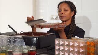 Beautiful African American female chocolatier working at her kitchen preparing handmade delicious candy. Professional confectioner working with hot melting chocolate. Food, dessert concept.