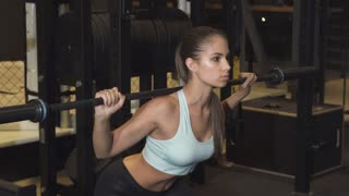 Beautiful athletic young sexy woman working out with a barbell at the gym doing squats confidence motivation energy effort agility active lifestyle lifting weights crossfit sport athletics muscles