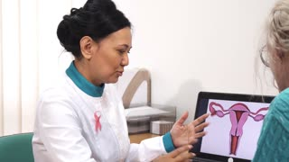 Beautiful female gynecologist working at the clinic showing uterus picture to her patient gynecology healthcare femininity communication medicine specialist friendly advise