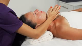 Beautiful happy mature woman receiving facial massage at beauty spa salon. Professional therapist doing neck and shoulders massage for female client. Relaxation, joy concept.