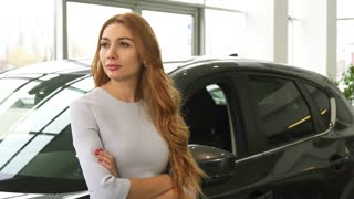 Beautiful happy red haired woman smiling dreamily posing with her newly bought auto at the dealership positivity success travelling discount offer sales rental service automotive transportation