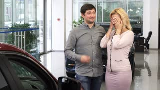 Beautiful mature woman receiving surprise at the dealership salon looking excited hugging her husband after he presented her a new car family love gift affection ownership consumerism buy