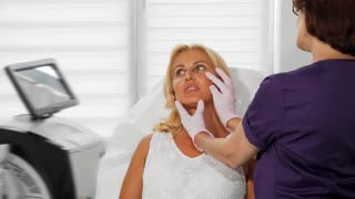 Beautiful mature woman talking to her cosmetologist during skin examination. Professional beautician examining skin of her female client. Dermatologist working with her patient.