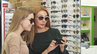 Beautiful red haired woman and her friend wearing sunglasses smiling taking selfies at the optics store technology smart phone social media mobility optometrist shop shopping buying fun