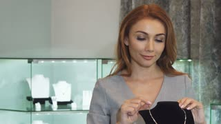 Beautiful sexy woman smiling excitedly trying on an expensive diamond necklace at the jewelry boutique beauty femininity elegance grace purchasing consumerism buying shopping sales