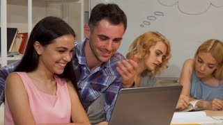 Beautiful young female student and her male friend smiling to the camera while working on a computer together. Two classmates preparing for exams. Technology, online, internet concept.
