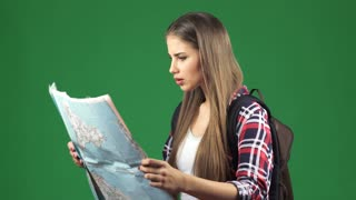 Beautiful young female tourism examining a map looking for her destination with a confused face on green chromakey background tourism travelling vacation lost navigation location puzzled.