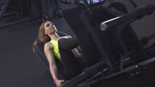 Beautiful young sportswoman working out at the gym doing leg press exercise. Attractive fit and toned fitness woman training at sports studio using leg press machine. Motivation, bodybuilding.