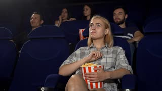 Beautiful young woman eating popcorn at the cinema, enjoying watching movies. Attractive female spectator relaxing at the movie theatre. Entertainment, lifestyle, weekend concept.
