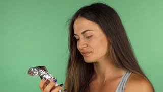 Beautiful young woman looking disgusted, while tasting dark chocolate on green chromakey background. Healthy eating and dieting concept. Female hating chocolate.