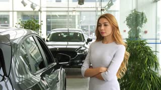 Beautiful young woman looking thoughtfully at the new car while choosing automobile to buy at the dealership showroom thinking doubting consumerism buying retail purchase luxury drive