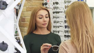 Cheerful beautiful young woman trying pair of new sunglasses at the optometrist store shopping with her best friend communication fashion consumerism friendship sale retail eyewear advise