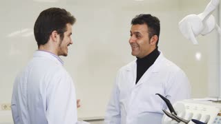 Cheerful handsome mature male dentist shaking hands with his younger colleague at the dental clinic partnership success medical team healthcare achiving doctors dentistry hospital