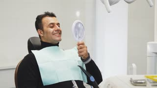 Cheerful handsome mature male patient sitting in the dental chair looking in the mirror smiling showing thumbs up curing cavity treatment health medicine dentistry clinical examination