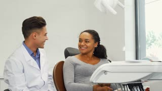 Cheerful young beautiful African woman talking selfie with her dentist after dental examination. Handsome male dentist talking selfie with his female patient after medical appointment.