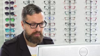 Close up of a bearded mature male professional optometrist smiling to the camera joyfully working on a computer at his eyewear store optician occupation profession job service concept.