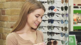 Close up of a beautiful happy woman trying on sunglasses shopping at the eyewear store consumerism fashion style beauty happiness wellbeing optics retail sale discount lifestyle price