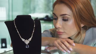 Close up of a beautiful sad woman looking unhappy and disappointed posing with an expensive diamond necklace not able to afford the purchase jewelry store buying money credit loan