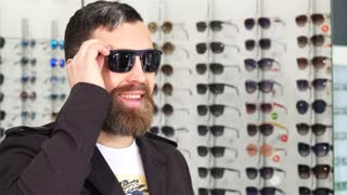 Close up of a cheerful mature bearded handsome man taking off sunglasses smiling to the camera while shopping at the eyewear store optometry UV protection optician consumerism.