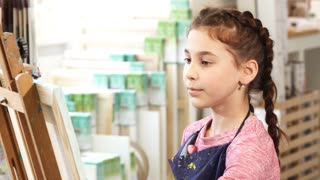 Close up of a cute pretty little girl wearing apron concentrating working on her painting during art class at school. Child painter enjoying drawing at art studio hobby lifestyle creating artwork.